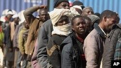 Buruh migran dari Afrika tiba dengan kapal mereka dari Misrata menunggu evakuasi IOM di pelabuhan Benghazi (5-5-2011). IOM imbau tegakkan perlindungan terhadap migran dalam perangi penyelundupan dan perdagangan manusia.
