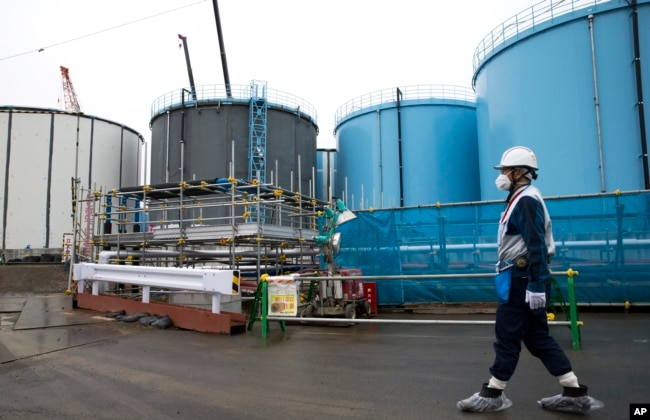 Employee walks past storage tanks for contaminated water at the tsunami-crippled Fukushima Dai-ichi nuclear power plant of the Tokyo Electric Power Co. in Okuma town, Fukushima prefecture, Japan, Feb. 23, 2017.