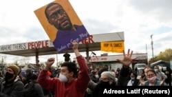 在明尼苏达州明尼阿波利斯市乔治·弗洛伊德广场,举着弗洛伊德画像的民众在听到前明尼苏达警察肖文被判有罪后发出欢呼。(2021年4月20日)