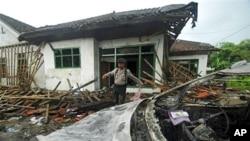 Polisi menginspeksi kerusakan rumah anggota jemaah Ahmadiyah setelah diserang di Banten. (Foto: AP)