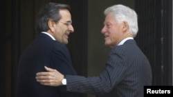 Greek Prime Minister Antonis Samaras (L) welcomes visiting former U.S. President Bill Clinton during their meeting in Athens July 22, 2012.