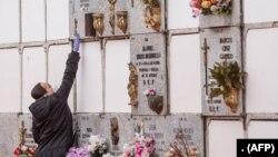 میڈرڈ کے قبرستان میں ایک خاتون کرونا وائرس سے ہلاک شخص کی تدفین کے موقع پر دیوار پر لگے کتبے کو چھو رہی ہیں