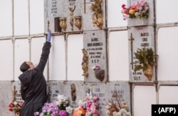 A woman wearing a face mask and gloves touches a niche during the burial of a man who died of the new coronavirus at the South Municipal cemetery in Madrid, on March 23, 2020.