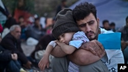 FILE - A Syrian refugee child sleeps on his father's arms while waiting at a resting point to board a bus, after arriving on a dinghy from the Turkish coast to the northeastern Greek island of Lesbos, Oct. 4 , 2015.