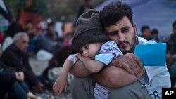 Một em bé tỵ nạn Syria ngủ trên cánh tay của cha mình. Thổ Nhĩ Kỳ bị quy trách đã không giúp đỡ người tỵ nạn, khiến số người tỵ nạn chiến tranh tìm đường đi châu Âu với làn sóng ngày càng gia tăng.