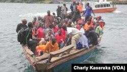Des rescapés du naufrage sur le lac Kivu lundi 30 novembre transportés dans une pirogue motorisée. Vingt-cinq personnes dont un enfant ont été repêchées après qu'un canot rapide a chaviré dans le lac Kivu. VOA/Charly Kasereka