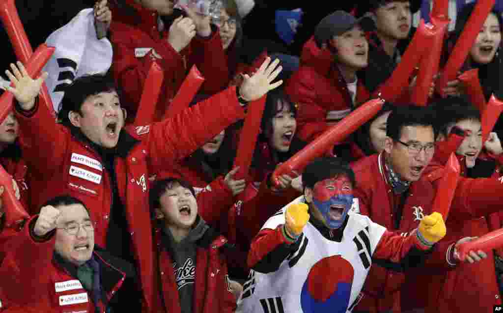South Koreans celebrate as their fellow countryman Lee Seung-hoon competes during the men's 10,000 meters speedskating race at the Gangneung Oval at the 2018 Winter Olympics in Gangneung, South Korea.
