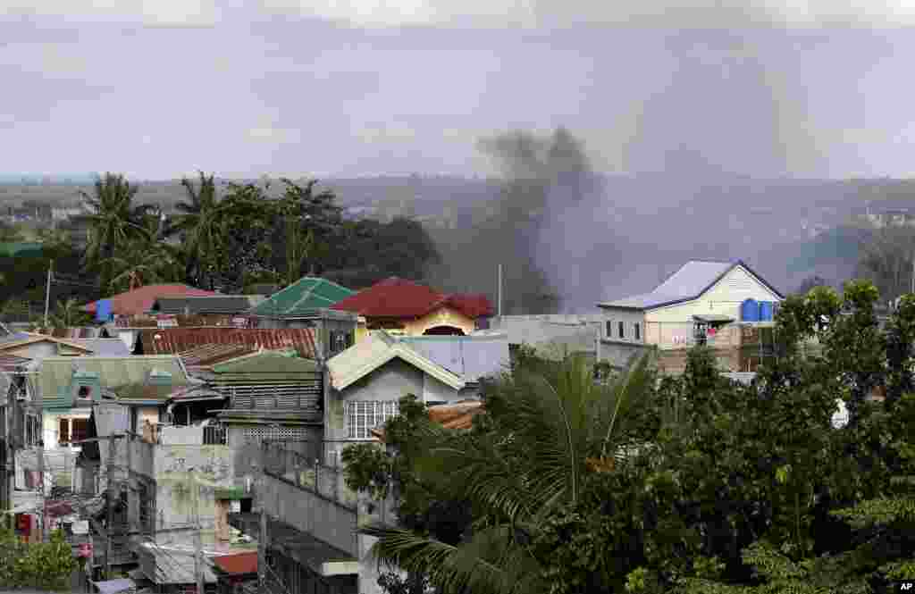 Smoke rises from a neighborhood where Muslim rebels are holding scores of hostages as human shields in Zamboanga, Philippines, Sept. 10, 2013.