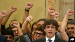 FILE - Catalan President Carles Puigdemont sings the Catalan anthem inside the parliament after a vote on independence in Barcelona, Spain, Oct. 27, 2017.