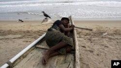 Ngư dân nằm ngủ trong thuyền đánh cá tại bờ biển Puri trong vùng vịnh Bengal. Nhà chức trách Ấn Độ đã công bố lệnh cảnh báo bão lớn.