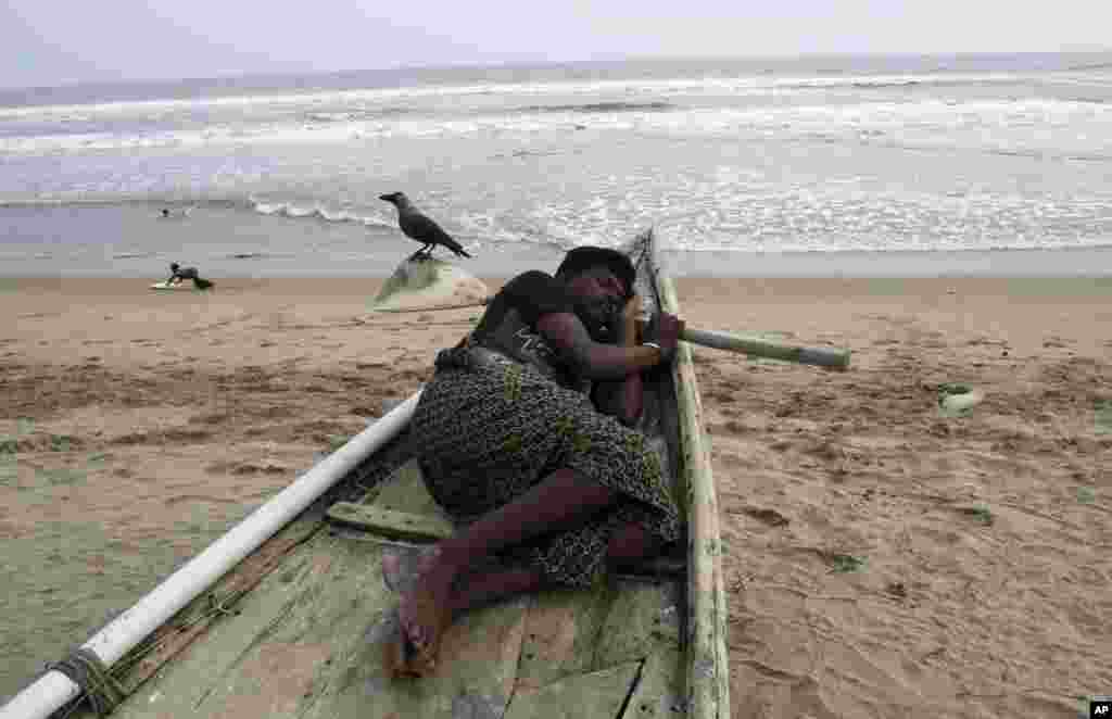 A child plays as an Indian fisherman sleeps in his anchored fishing boat on the Bay of Bengal coast at Puri, Odisha state, India, Oct. 10, 2013.