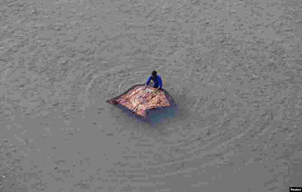 A man washes a blanket on the banks of the river Tawi in Jammu, India.