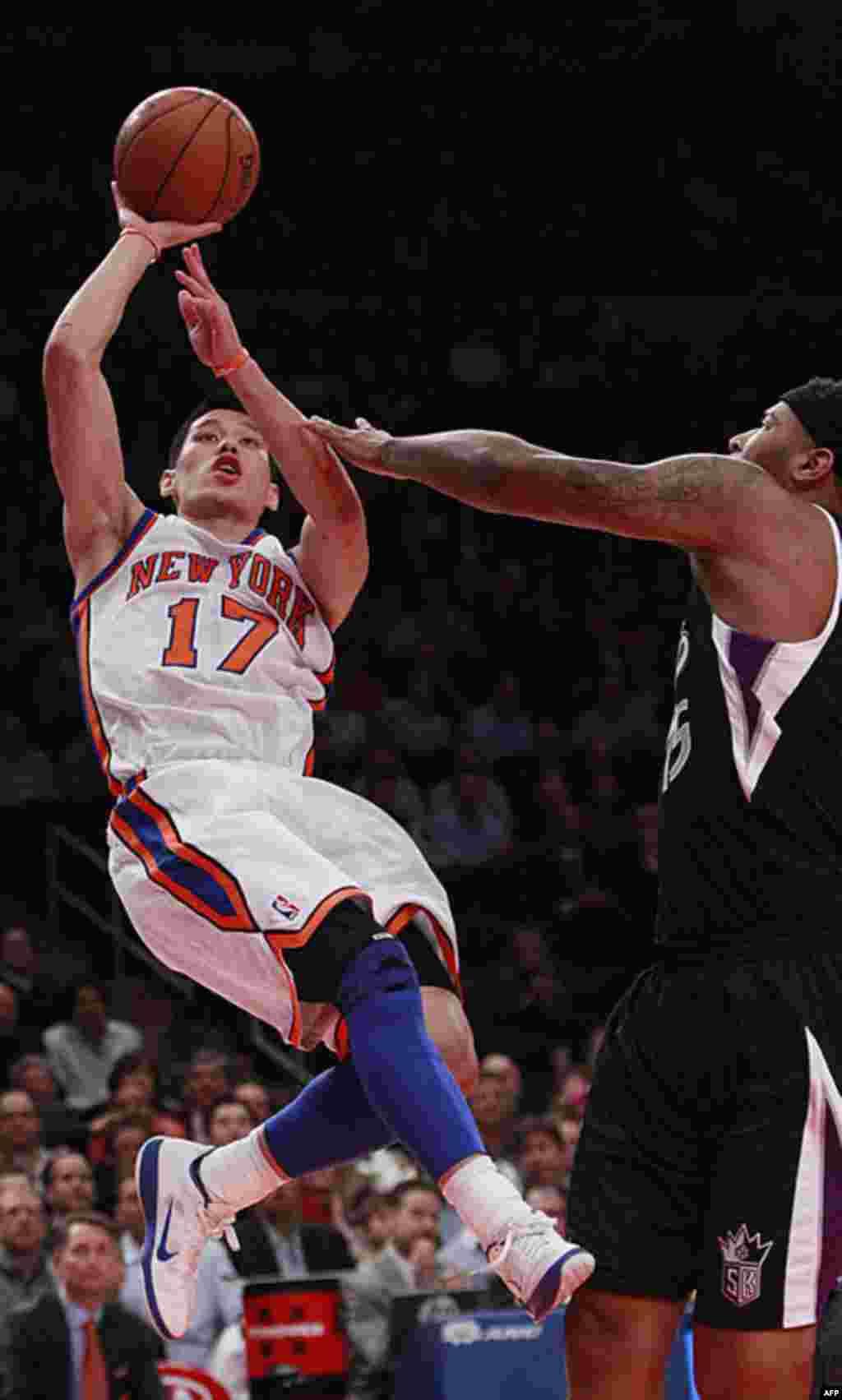 Jeremy Lin của đội New York Knicks vượt lên Demarcus Cousins của đội Sacramento Kings ném banh vào rổ trong trận đấu của Hiệp hội Bóng rổ Quốc gia (NBA) hôm 15/2/12 (AP)