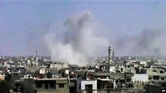 In this image from an amateur video and released by the Syrian Media Council, smoke rises following purported shelling in Homs, Syria, April 10, 2012.