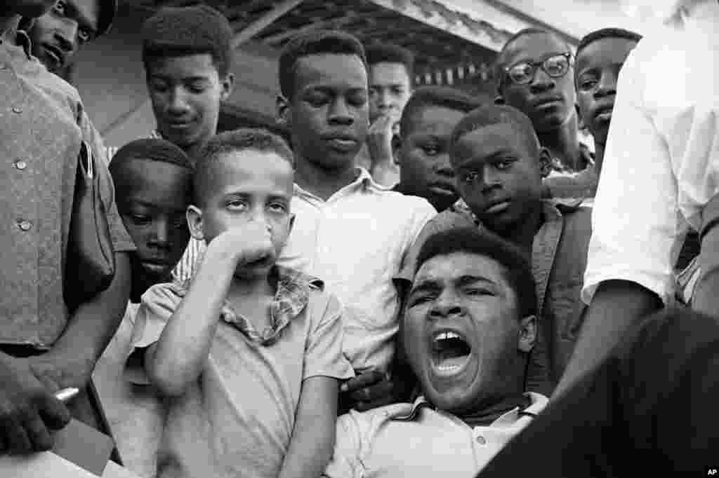 "FILE - Heavyweight Champion Muhammad Ali exclaims ""Why me?"" when informed his draft board in Louisville, Ky., had reclassified him 1-A in the draft, Feb. 17, 1966. Ali surrounded himself with youngsters from his neighborhood as he told of his feelings in"