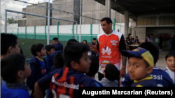 Eduardo David Rodriguez, 40, gives instructions to children at a soccer school he manages for hobby, in Lomas de Zamora, on the outskirts of Buenos Aires, Argentina September 28, 2021. . (REUTERS/Agustin Marcarian)