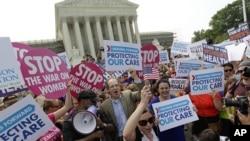 Partidarios de la ley de Salud celebran en las afueras de la Corte Suprema donde el tribunal falló a favor de sostener el seguro de Salud obligatorio.