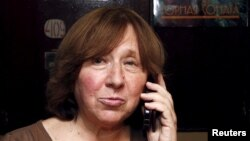 Svetlana Alexievich speaks on the phone as she walks out of her apartment in Minsk, Belarus, Oct. 8, 2015.