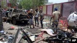 Para pejuang yang setia kepada pemerintah berkumpul di lokasi bom mobil bunuh diri di Aden, Yaman selatan (29/8). (AP/Wael Qubady)