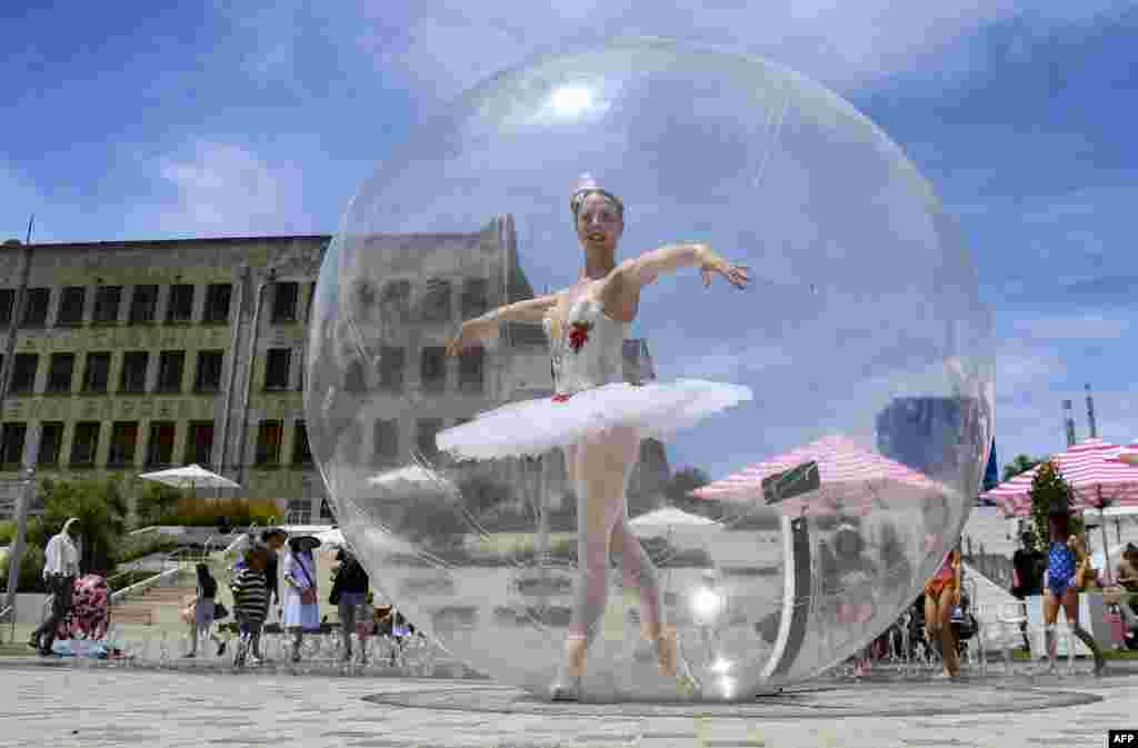 A ballet dancer poses in a giant plastic bubble as she entertains Christmas shoppers in Melbourne, Australia.
