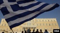 Para demonstran melakukan protes atas langkah penghematan pemerintah di depan gedung parlemen Yunani di Athena, Sabtu (18/6).