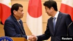 ທ່ານ Rodrigo Duterte ປະທານາທິບໍດີຟີລິບປິນ ຈັບມືກັບນາຍົກລັດຖະມົນຕີຍີ່ປຸ່ນ ທ່ານ Shinzo Abe ພາຍຫລັງສິ້ນສຸດພິທີເຊັນສັນຍາ ແລະຖະແຫລງການຮ່ວມກັນ ຢູ່ທີ່ບ້ານພັກທາງການຂອງທ່ານ Abe ຢູ່ນະຄອນໂຕກຽວ ໃນວັນທີ 30 ຕຸລາ, 2017.
