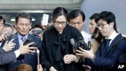 Former Korean Air executive Cho Hyun-ah, center, is surrounded by reporters as she leaves the Seoul High Court in Seoul, South Korea, Friday, May 22, 2015.
