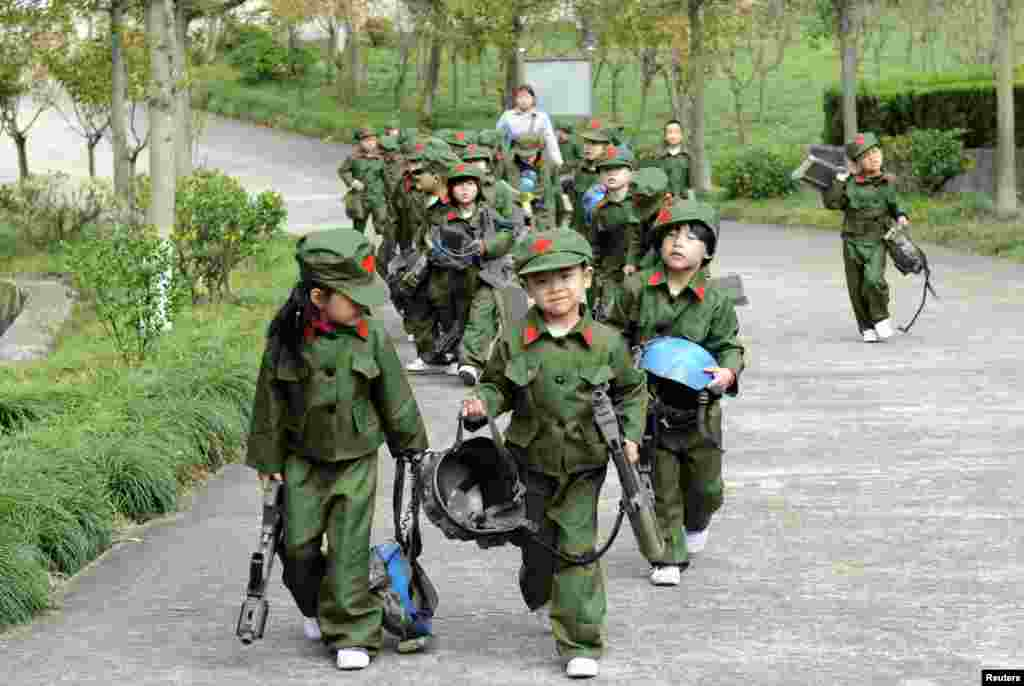 Kindergarten children dressed in military uniforms carry toy guns at a park in Dongyang, Zhejiang province, China.