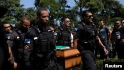 Policemen carry the coffin of military police officer Felipe Santos Mesquita, who was shot dead during a clash with drug gangs in Rocinha slum, during the burial in Rio de Janeiro, Brazil, March 23, 2018.