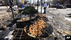 ຜູ້ຄົນພວມພາກັນຫຸ້ມເບິ່ງ ບ່ອນລະເບີດແຕກ ທີ່ຕະຫຼາດຂາຍຜັກແຫ່ງນຶ່ງ ໃນເມືອງ Basra (15 ກັນຍາ 2013)
