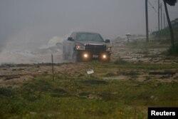 Una camioneta avanza sobre una carretera inundada cuando el huracán Michael avanza por Alligator Point, en Florida. Octubre 10 de 2018. Reuters/Carlo Allegri.