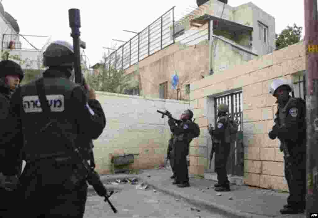Israeli riot police shoot tear gas at Palestinian youth, not seen, during a protest against Jewish settlements in the east Jerusalem neighborhood of Silwan, Monday, Dec. 27, 2010. Tensions regularly run high in Silwan, where a small group of Israeli settl