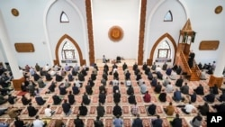 Bosnian muslims, some wearing face masks to protect themselves from the COVID-19 infection, attend Eid al-Fitr prayers in Sarajevo, Bosnia, Sunday, May 24, 2020.