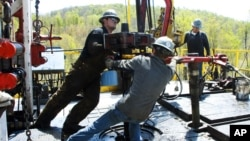 Workers work on a Chesapeake Energy natural gas well site near Burlington, Pennsylvania. New techniques are increasing oil production in the U.S.