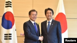 FILE - South Korea's President Moon Jae-in, left, shakes hands with Japan's Prime Minister Shinzo Abe, right, before their meeting at Abe's official residence in Tokyo, Japan, May 9, 2018.