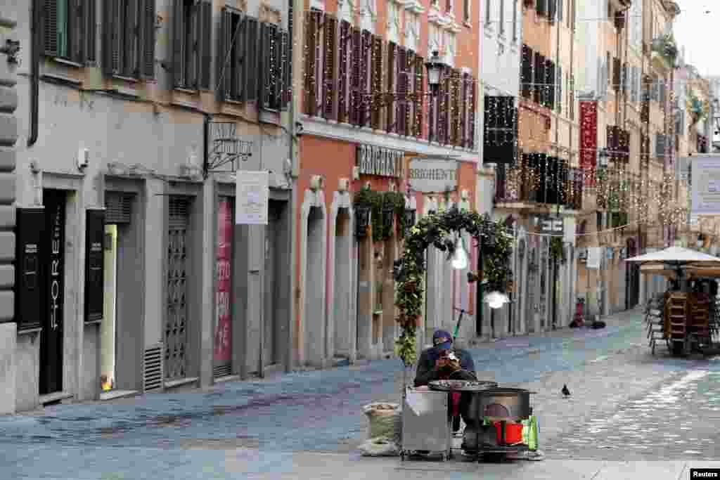 Seorang pedagang kaki lima yang menjual kacang chestnut panggang di Via Frattina menunggu pengunjung yang sepi, ketika Italia menerapkan kembali lockdown total selama musim Natal untuk mengekang penyebaran COVID-19 di Roma, Italia, 24 Desember 2020.