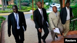 M23 rebel negotiators are seen heading into the final leg of negotiations with the Congolese government, in Kampala, Oct. 19, 2013.