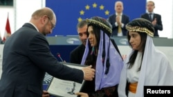 Nadia Murad Basee Taha (C) and Lamiya Aji Bashar (R), both Iraqi women of the Yazidi faith receive their 2016 Sakharov Prize from European Parliament President Martin Schulz (L) during an award ceremony at the European Parliament in Strasbourg, France, De