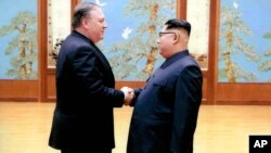 En esta imagen divulgada por la Casa Blanca, el secretario de Estado, Mike Pompeo saluda a Kim Jong Un durante su primera visita a Corea del Norte.