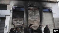 В ході заворушень в Афінах сильно постраждав центр міста. На фото - люди ідуть повз обвуглену вітрину Євробанку.
