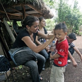 A migrant from Honduras wipes her son's face during a rest stop on the seven hour journey through the Peten Jungle in northern Guatemala (File)