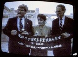 资料照:电视画面显示,来自加州的民主党众议员南希·佩洛西(中)、来自乔治亚州的民主党众议员本·琼斯(左)和来自华盛顿州的共和党众议员约翰·米勒在天安门广场展示横幅,向为中国民主事业牺牲的烈士致敬。(1991年9月4日)