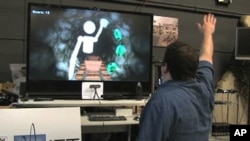 Evan Suma demonstrates a simulation with Microsoft's Kinect video game accessory that can help patients undergo physical therapy at USC's Institute for Creative Technologies