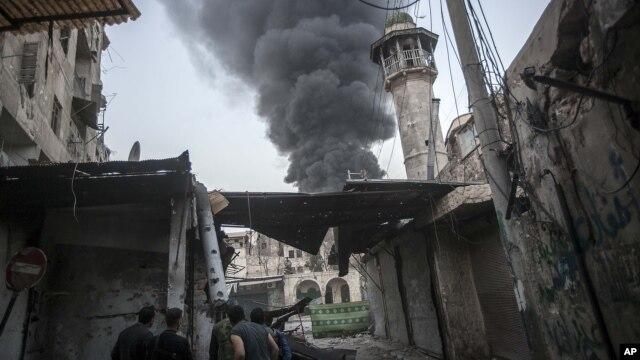 Khói bốc lên sau các vụ pháo kích vào thị trấn Jedida trong thành phố Aleppo.