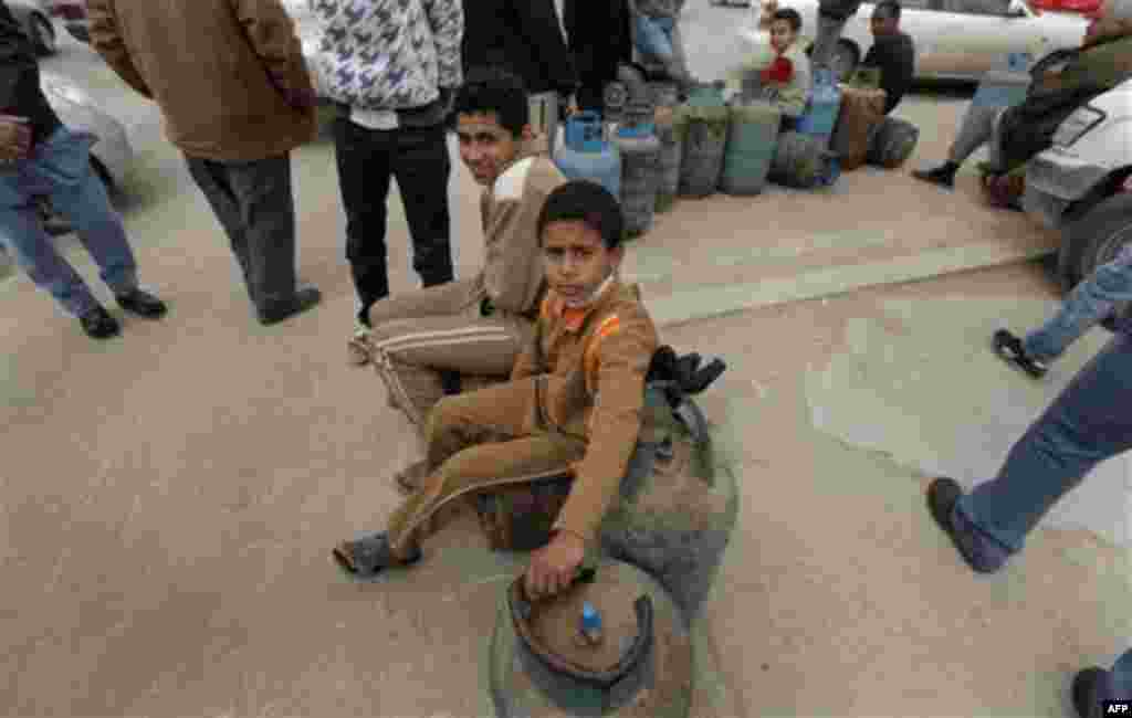 Two Libyan children wait by empty cooking gas cylinders as they queue in front of a cooking gas storage house in Benghazi, Libya Sunday, March 13, 2011. Libyans queued during the day in Benghazi for cooking gas in front of storage houses that suffer sever
