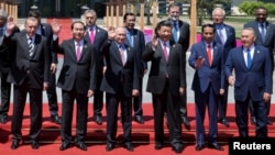 Leaders attending the Belt and Road Forum wave as they pose for a group photo at the Yanqi Lake venue on the outskirt of Beijing, China, May 15, 2017