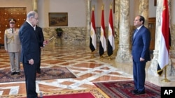 FILE - In this photo provided by Egypt's state news agency MENA, Egyptian President Abdel-Fattah el-Sissi, right, presides over the swearing in of Prime Minister Sheriff Ismail, in Cairo, Sept. 12, 2015.