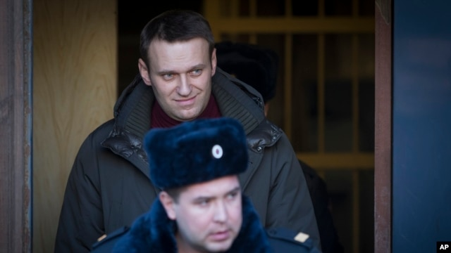 Russian opposition activist Alexei Navalny, top, surrounded by police officers leaves a court after he had been sentenced to seven days in prison after participating in an anti-government protest in Moscow, Feb. 25, 2014.