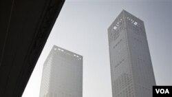 Seorang perokok berjalan diantara gedung-gedung pencakar langit berselimut debu polusi di Beijing (22/11).
