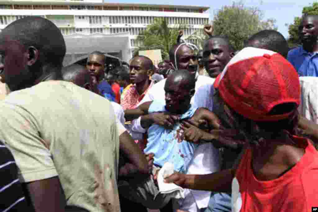 An injured man is carried past the National Assembly building as thousands demonstrated against proposed constitutional changes, in central Dakar, Senegal Thursday, June 23, 2011. Senegalese police lobbed tear gas at thousands of protesters who amassed in